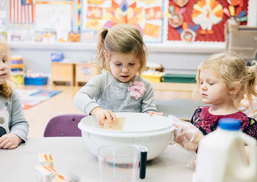 Two preschool girls using a mixing bowl to cook