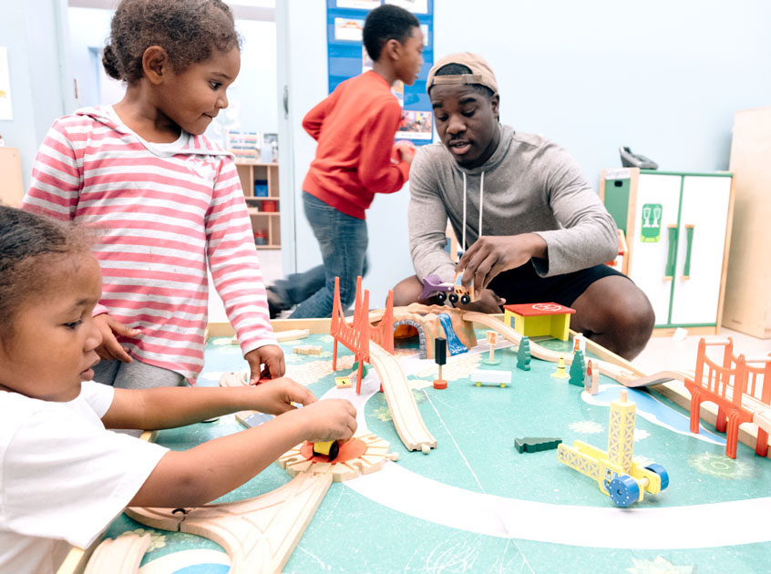 Man playing with toy trains with children