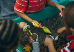 Three young children playing in a dirt box during the Come Play! event at the Homewood Early Learning Hub.