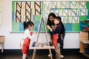 Picture: Two young children and their teacher standing, painting at an easel in a classroom. OCDEL Community Survey