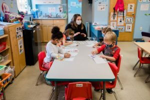 Image: An early learning professional sits at a table with several children who are working on a craft activity.
