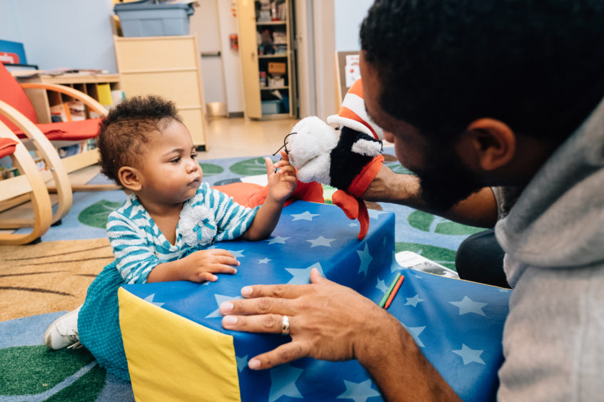 A baby and adult male caregiver share a close interaction as the caregiver interacts puppets an orange and black toy.