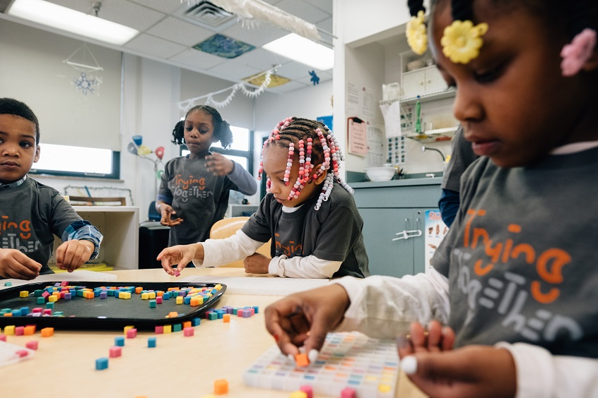 Image: Four young children play together in an early childhood classroom. Three of them sit at a table playing with small colorful blocks. One child stands beside the table watching the others play.