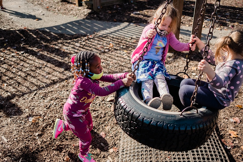 Image: Three children play together on a tire swing at a local playground.